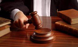 A judge hand striking a gavel over a table Foto: SalFalko